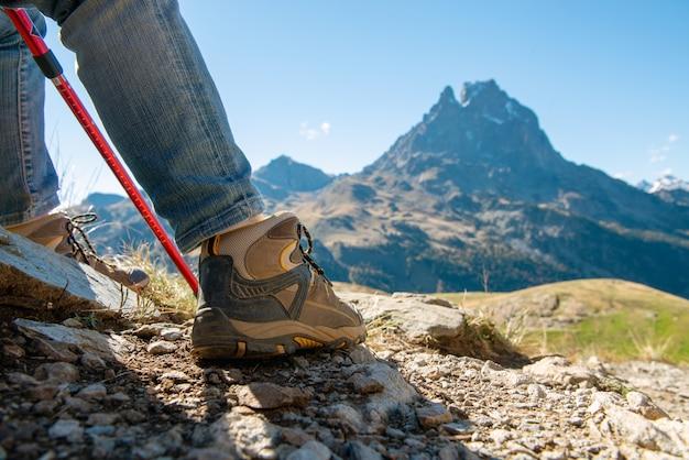 Chiuda in su delle scarpe della viandante il ossa di pic su priorità bassa