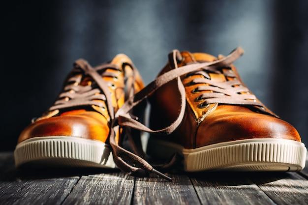 Chiuda in su delle scarpe di cuoio marroni degli uomini con i laccetti su fondo di legno scuro