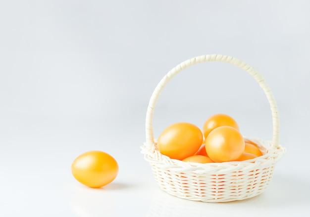 Chiuda in su delle uova di pasqua dorate in cestino bianco