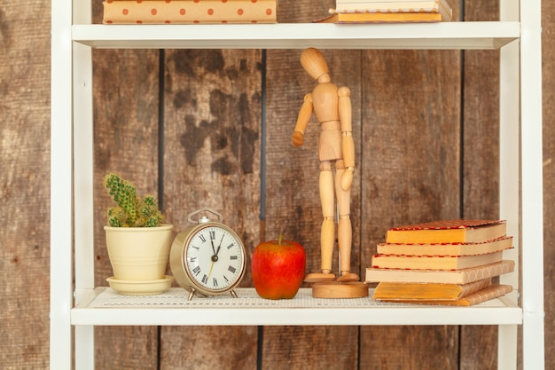 Chiuda in su dello scaffale per libri bianco contro la parete di legno del grunge
