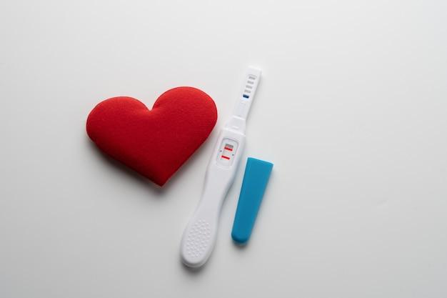 Chiuda in su dello strumento dell'esame di gravidanza su priorità bassa bianca.