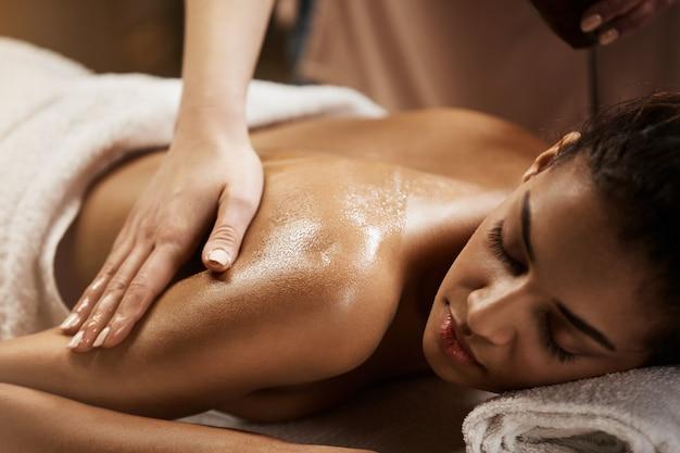Chiuda in su di bella donna africana che gode del massaggio nel salone della stazione termale.