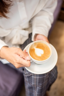Chiuda in su di bella donna sta bevendo il caffè