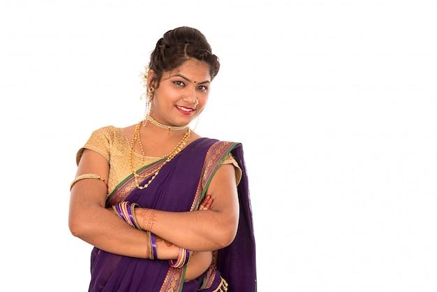 Chiuda in su di bella ragazza tradizionale indiana in saree su priorità bassa bianca