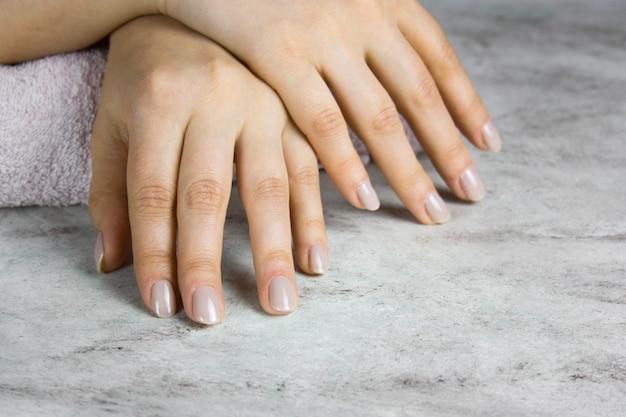 Chiuda in su di belle mani femminili con il manicure sulla tabella di marmo