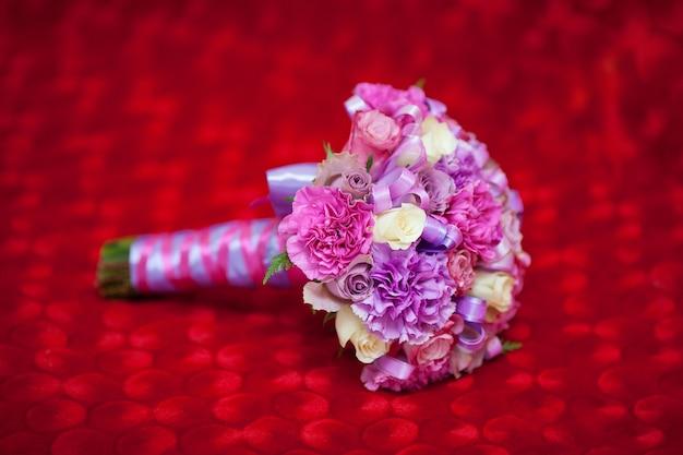 Chiuda in su di bello mazzo dentellare di cerimonia nuziale su tessuto rosso