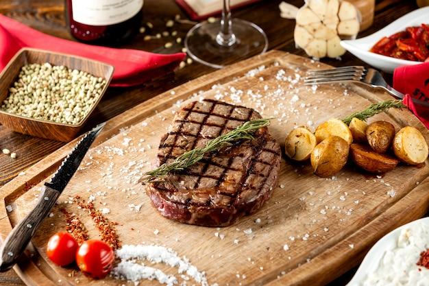 Chiuda in su di bistecca arrostita servita con la patata arrostita