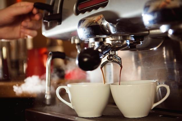 Chiuda in su di caffè espresso che versa dalla macchina del caffè in tazze bianche.