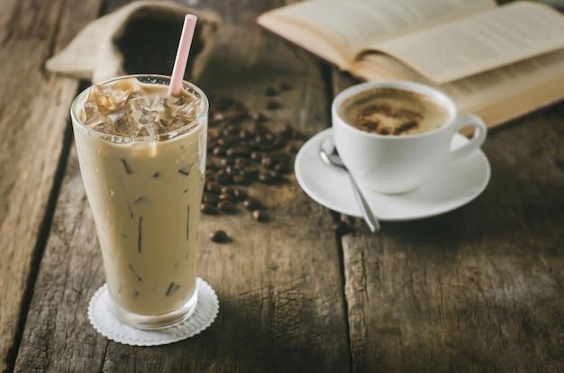 Chiuda in su di caffè ghiacciato sulla tabella di legno con la tazza di caffelatte e chicchi di caffè