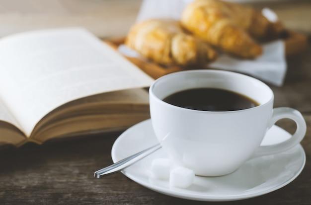 Chiuda in su di caffè nero con il libro e il croissant sulla tabella di legno