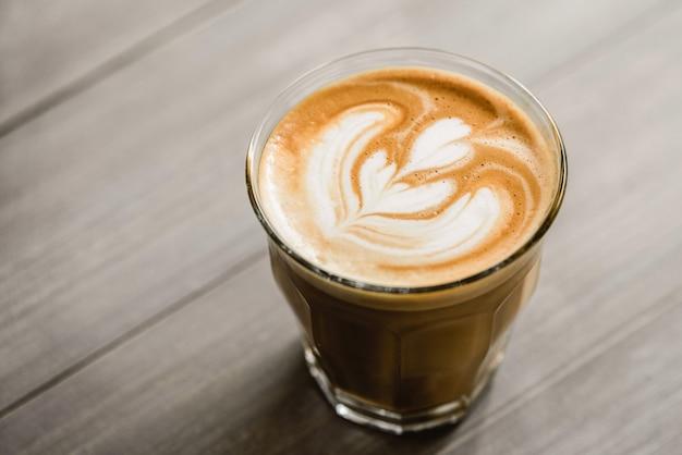 Chiuda in su di caffè preparato fresco in vetro di bicchiere con bella arte del latte sulla tavola di legno