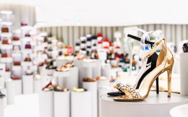 Chiuda in su di colore dorato e scarpe tacco alto di colore nero in un negozio