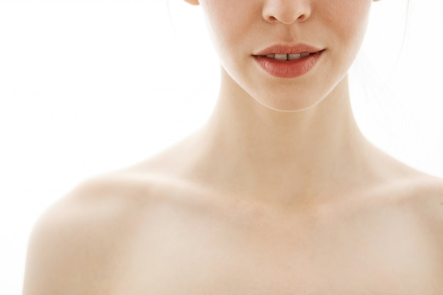 Chiuda in su di giovane bella donna nuda tenera sopra priorità bassa bianca. copia spazio.