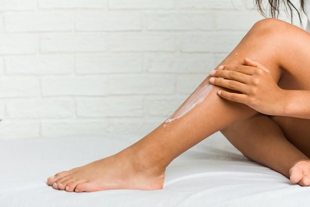 Chiuda in su di giovane donna afroamericana che ottiene la crema idratante sulle sue gambe