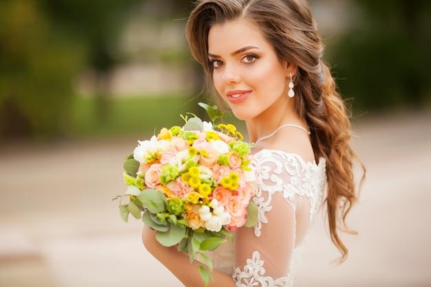 Chiuda in su di giovane donna con il mazzo di fiori