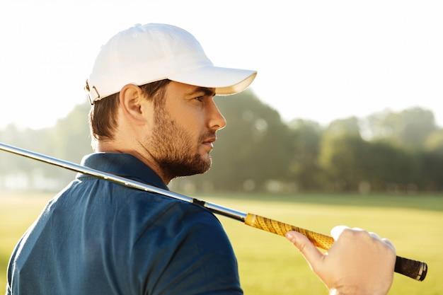 Chiuda in su di giovane giocatore di golf maschio bello in cappello