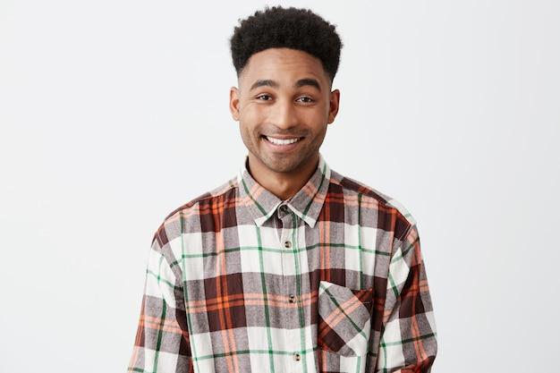 Chiuda in su di giovane maschio americano allegro dalla carnagione scura bello con capelli neri ricci in camicia a quadretti che sorride con i denti con l'espressione felice e rilassata del fronte.