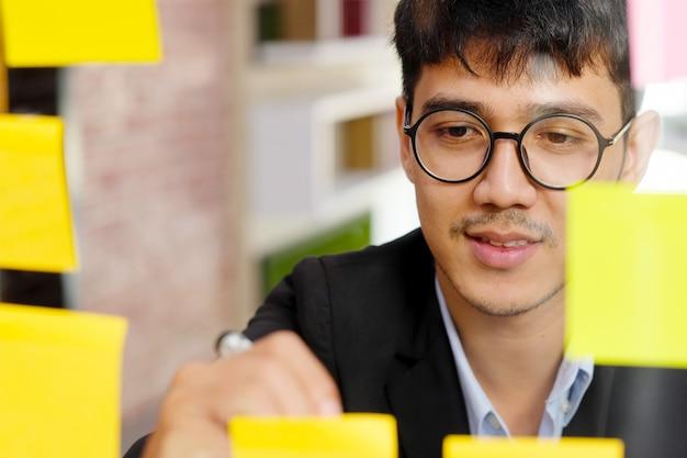 Chiuda in su di giovane uomo asiatico scrivendo sulla nota adesiva in ufficio, idee creative di brainstorming aziendale, stile di vita dell'ufficio, successo nel concetto di business