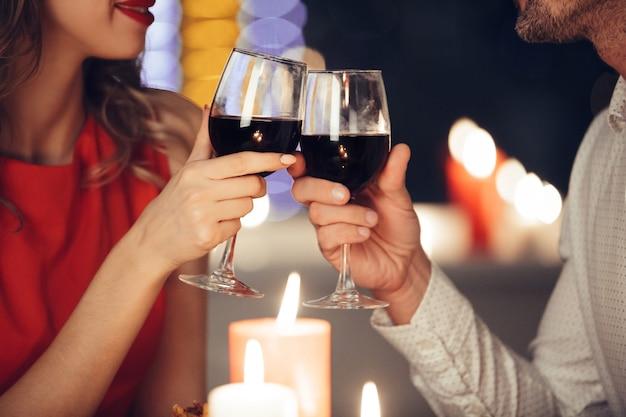 Chiuda in su di giovani coppie che tengono i vetri con vino