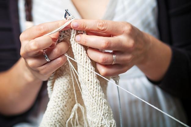 Chiuda in su di lavoro a maglia della giovane donna