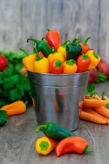 Chiuda in su di mini peperoni dolci variopinti in un cestino dell'annata