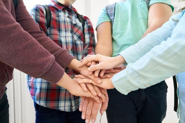 Chiuda in su di molte mani dei bambini che toccano, tenendo insieme l'un l'altro.