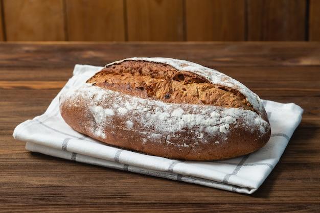 Chiuda in su di pane appena sfornato. pane di grano saraceno sul tovagliolo bianco