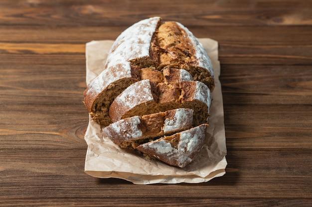 Chiuda in su di pane cotto affettato. pane di grano saraceno su carta da forno. superficie in legno e backgound