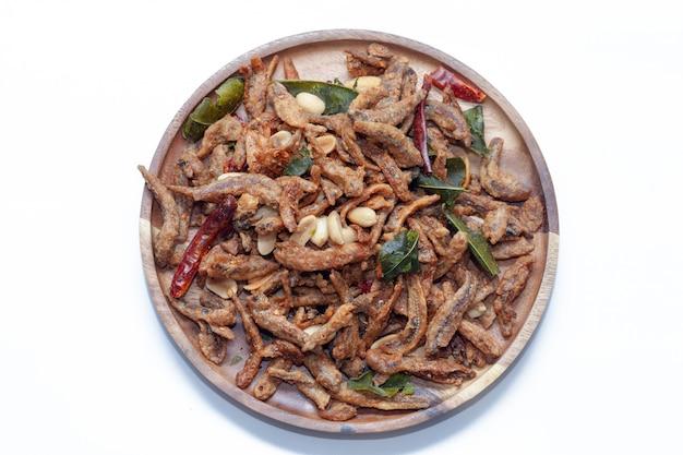 Chiuda in su di piccoli pesci fritti nel grasso bollente croccanti sul piatto