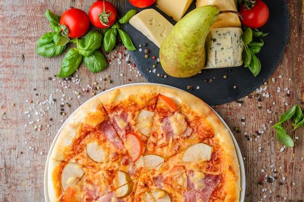 Chiuda in su di pizza con la pera e prosciutto su una priorità bassa di legno, vista superiore