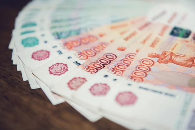 Chiuda in su di soldi, banconote russe di valuta delle macerie, sulla tabella di legno