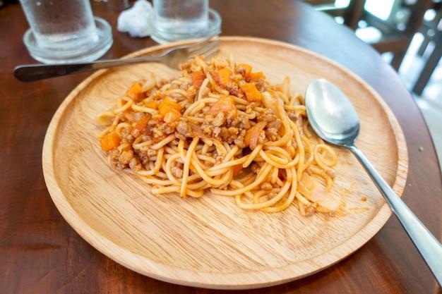Chiuda in su di spaghetti sul piatto di legno