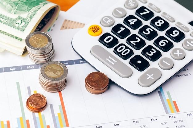 Chiuda in su di un calcolatore e delle monete su un affare