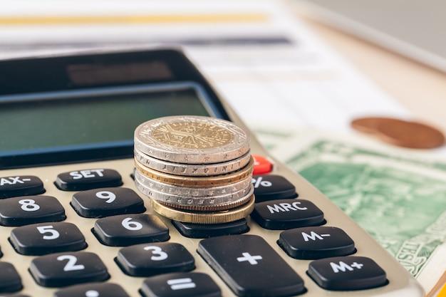 Chiuda in su di un calcolatore e delle monete su una priorità bassa di affari