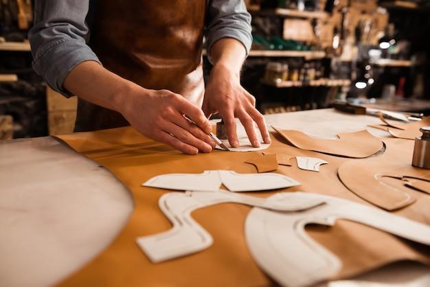 Chiuda in su di un calzolaio che misura e che taglia il cuoio