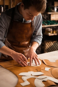 Chiuda in su di un calzolaio maschio che lavora con la tessile di cuoio