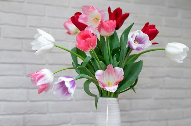 Chiuda in su di un mazzo di bei tulipani in un vaso su un muro di mattoni bianco.