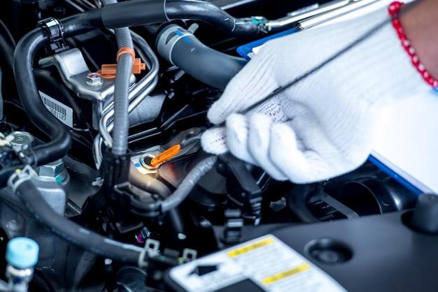 Chiuda in su di un meccanico di automobile che controlla il livello di olio in un'officina meccanica
