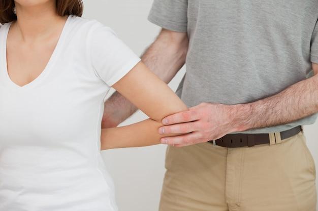 Chiuda in su di un medico che esamina il braccio di un paziente