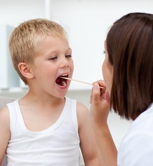 Chiuda in su di un medico che esamina la gola dei pazienti