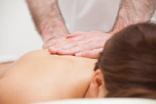Chiuda in su di un medico che massaggia la parte posteriore di una donna