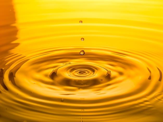 Chiuda in su di un olio di goccia su una priorità bassa gialla