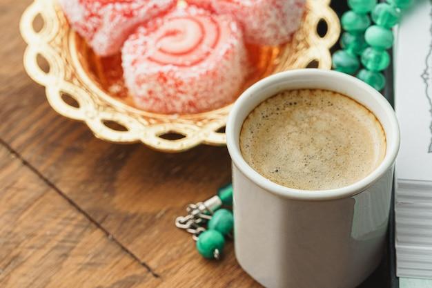 Chiuda in su di un piccolo piatto con i dolci e la tazza di caffè espresso turchi