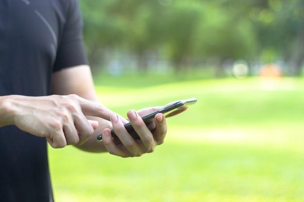 Chiuda in su di un uomo che usando lo smart phone mobile nero con lo spazio della copia per testo