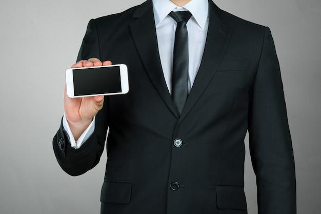 Chiuda in su di un uomo d'affari che per mezzo dello smartphone mobile