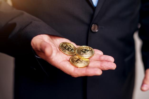 Chiuda in su di un uomo d'affari maturo in mani del vestito che tengono tre bitcoin.