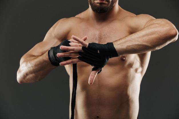 Chiuda in su di un uomo muscolare in buona salute che lega le fasciature di inscatolamento