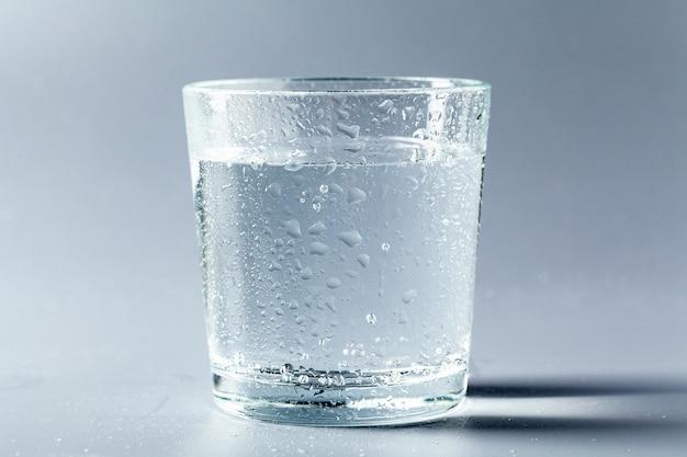 Chiuda in su di un vetro con acqua minerale