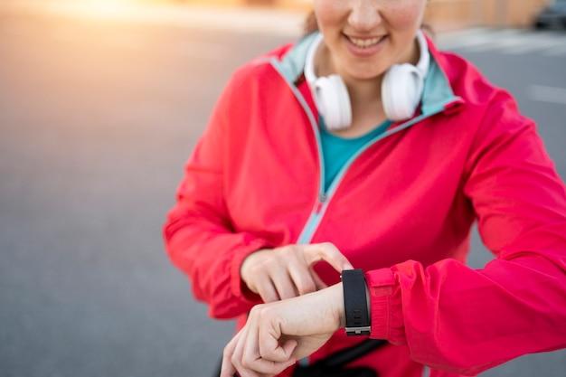 Chiuda in su di una cuffia da portare del corridore della giovane donna che esamina il suo orologio sportivo e che controlla i progressi sull'orologio astuto