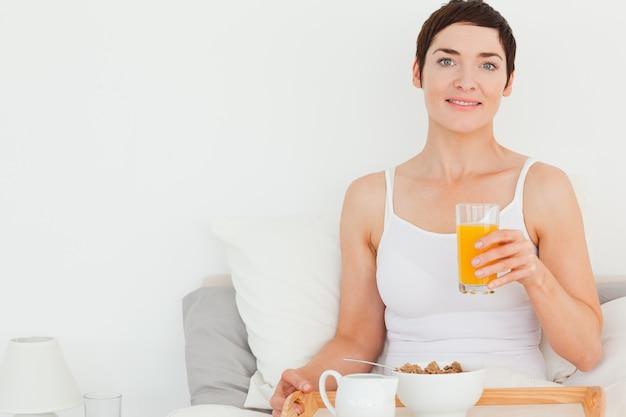 Chiuda in su di una donna che beve il succo di arancia